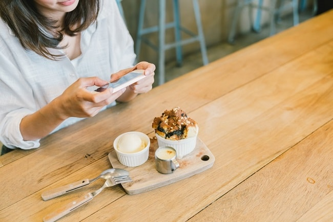 Woman capturing a photo on her food
